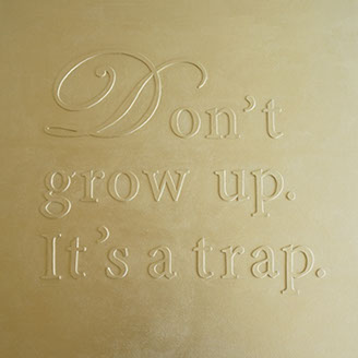 Don't grow up. It's a trap. Golden painting, phrase on canvas.