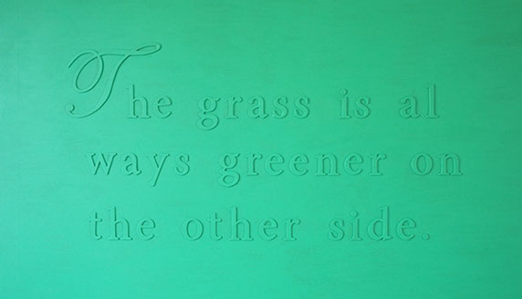 The grass is always greener on the other side. Green painting, phrase on canvas.